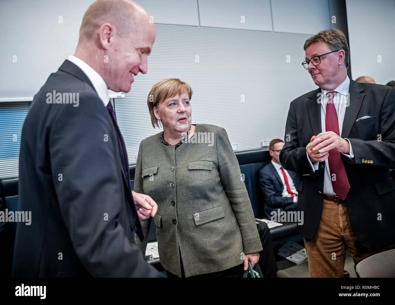 Berlin, Germany. 06th Nov, 2018. Chancellor Angela Merkel (CDU) comes to the parliamentary session between Ralph Brinkhaus (CDU, l), leader of the CDU/CSU parliamentary group in the Bundestag, and Michael Grosse-Brömer (CDU, r), first parliamentary director of the CDU/CSU parliamentary group in the Bundestag. Credit: Michael Kappeler/dpa/Alamy Live News - Stock Image