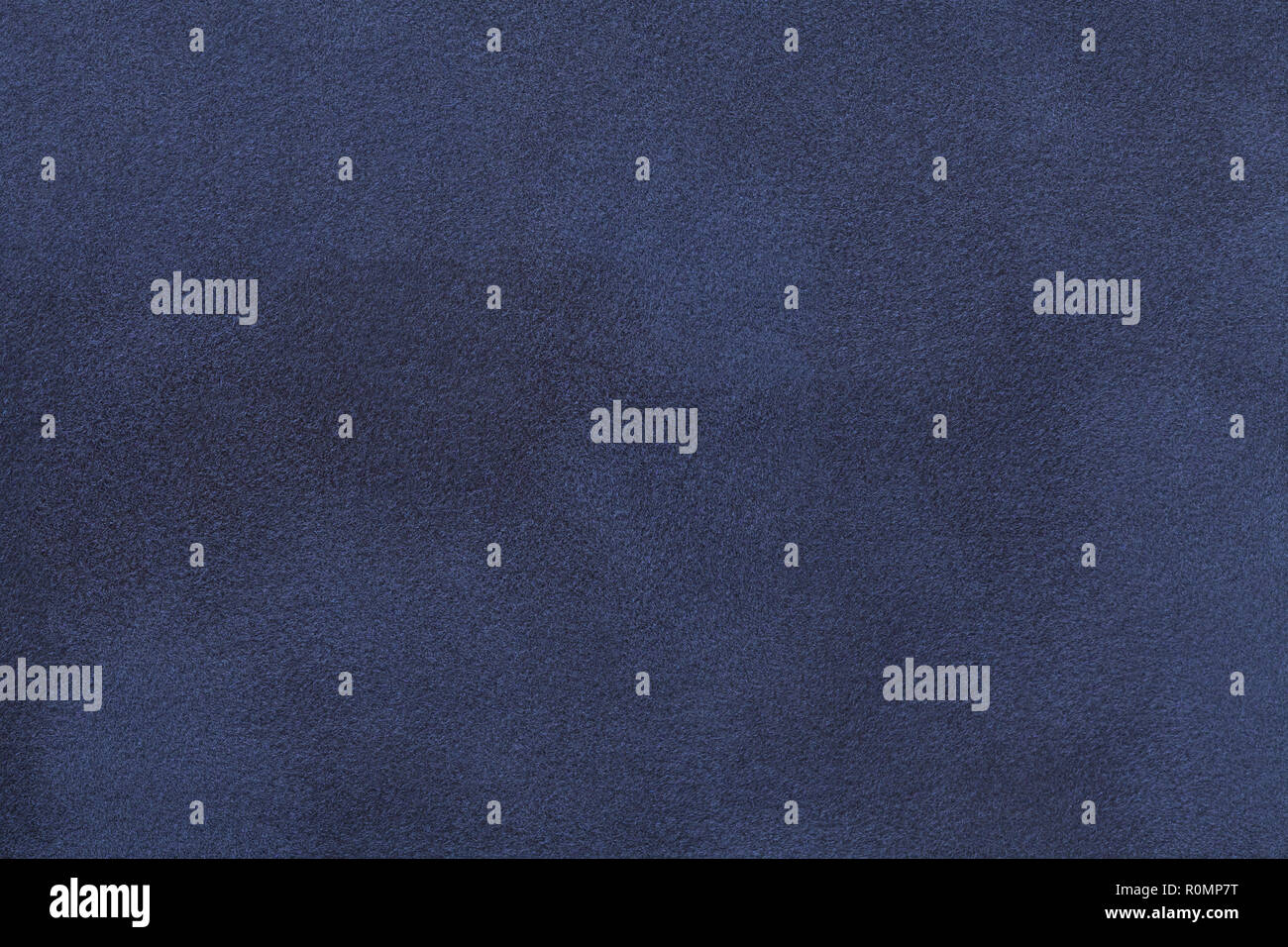 Navy blue matte background of suede fabric, closeup. Velvet texture of seamless denim leather. - Stock Image