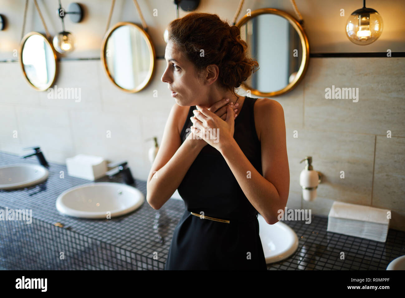 Young brunette woman in elegant black dress touching her throat while standing in toilet - Stock Image