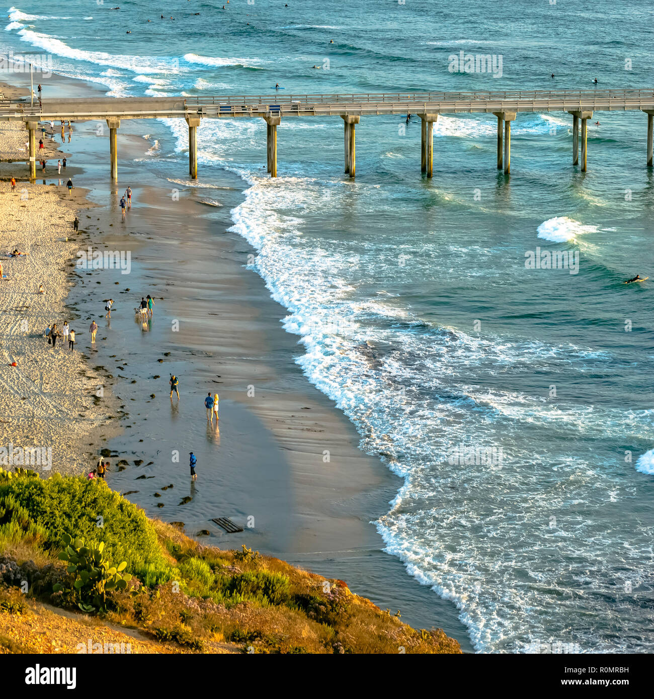 Scripps Pier and people at Pacific Ocean shoreline - Stock Image