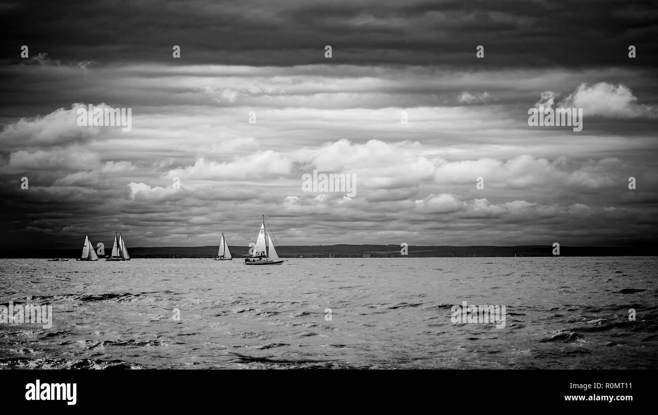 Boat sailing in the upcomming storm. Sailboat in bad weather sail at opened sea. Sailing yacht under heavy cloud sky. Stock Photo