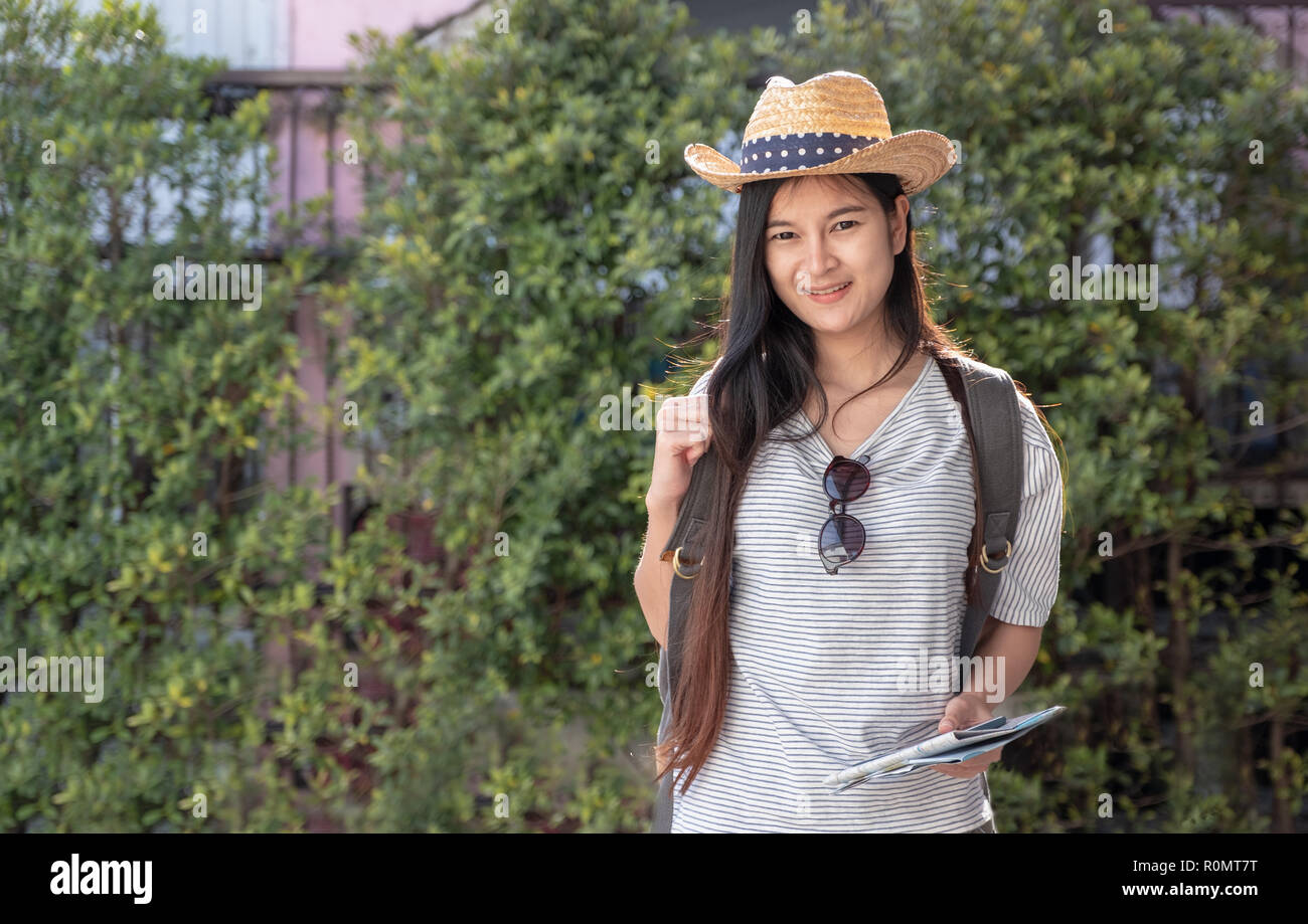 Asian woman traveler backpacker looking for route of place with map on street in when travel in city,journey trip - Stock Image