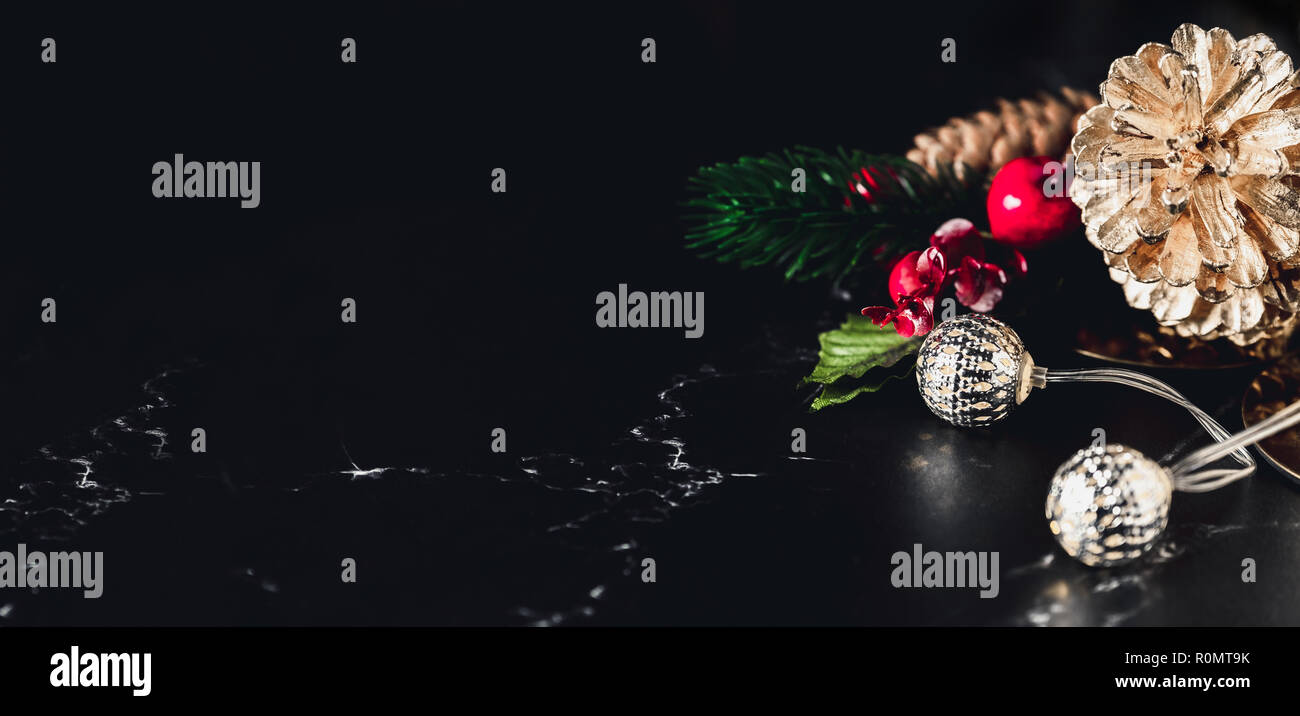 Glowing light string and pine cone and mistletoe decoration on marble table and blue background.Winter holiday greeting card.banner for display of des - Stock Image