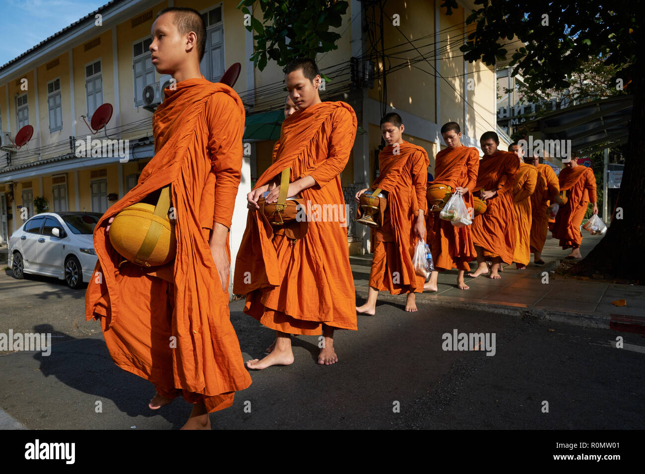 Novice monks or Samanen of Wat Mahathat in Bangkok, Thailand, during their early morning alms round in the temple's vicinity - Stock Image