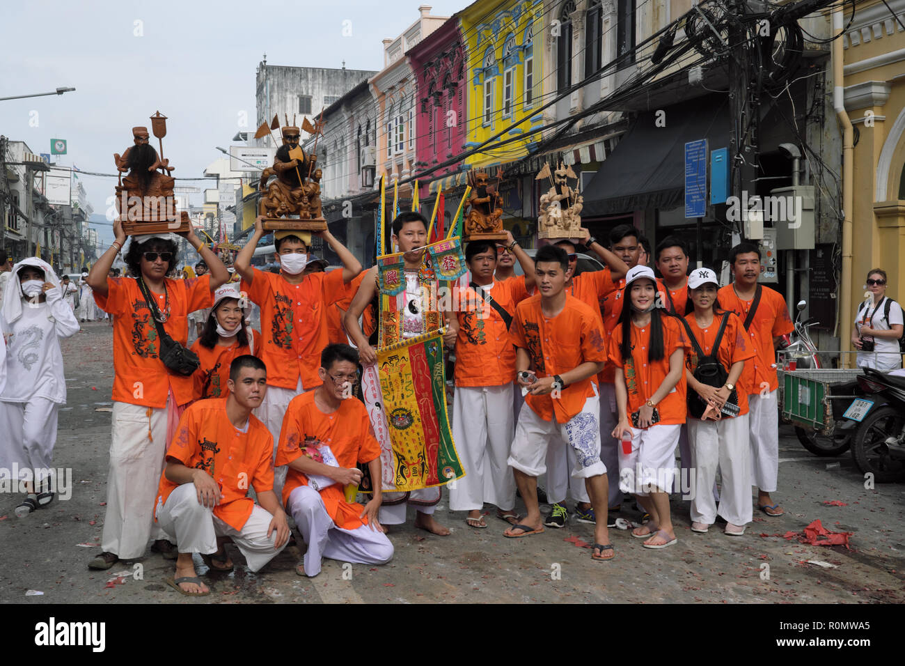 Participants in a procession during the Vegetarian Festival, Phuket Town, Thailand, pose for photos, some holding the figures of Chinese Emperor Gods - Stock Image