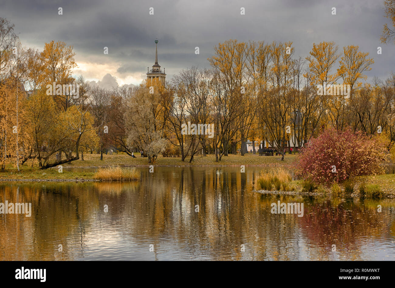 Autumn landscape in Victory Park and a house with a spire in the style of Stalinist Neoclassicism (Saint-Petersburg) - Stock Image