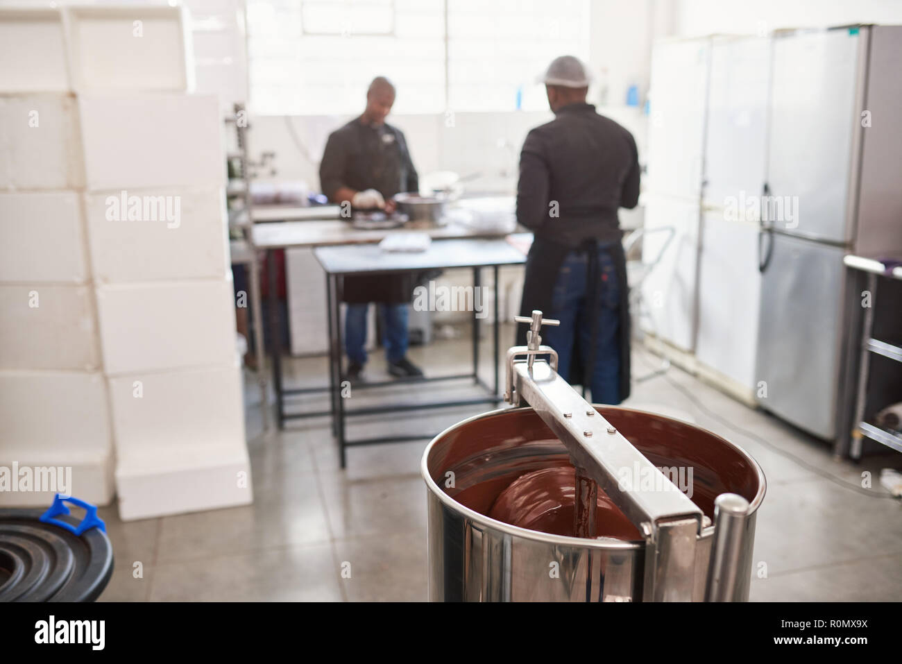 Workers preparing ingredients in a chocolate making factory - Stock Image