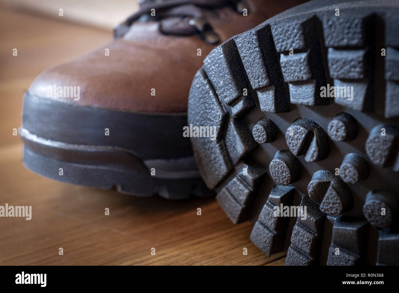 Deep tread lugs on the soles of a new pair of walking boots. - Stock Image
