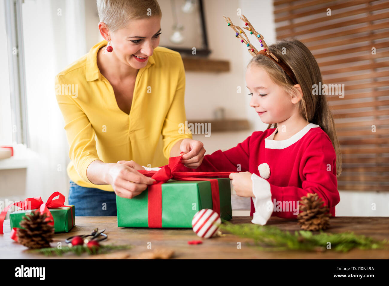 Family Christmas Gifts.Mother And Daughter Having Fun Wrapping Christmas Gifts