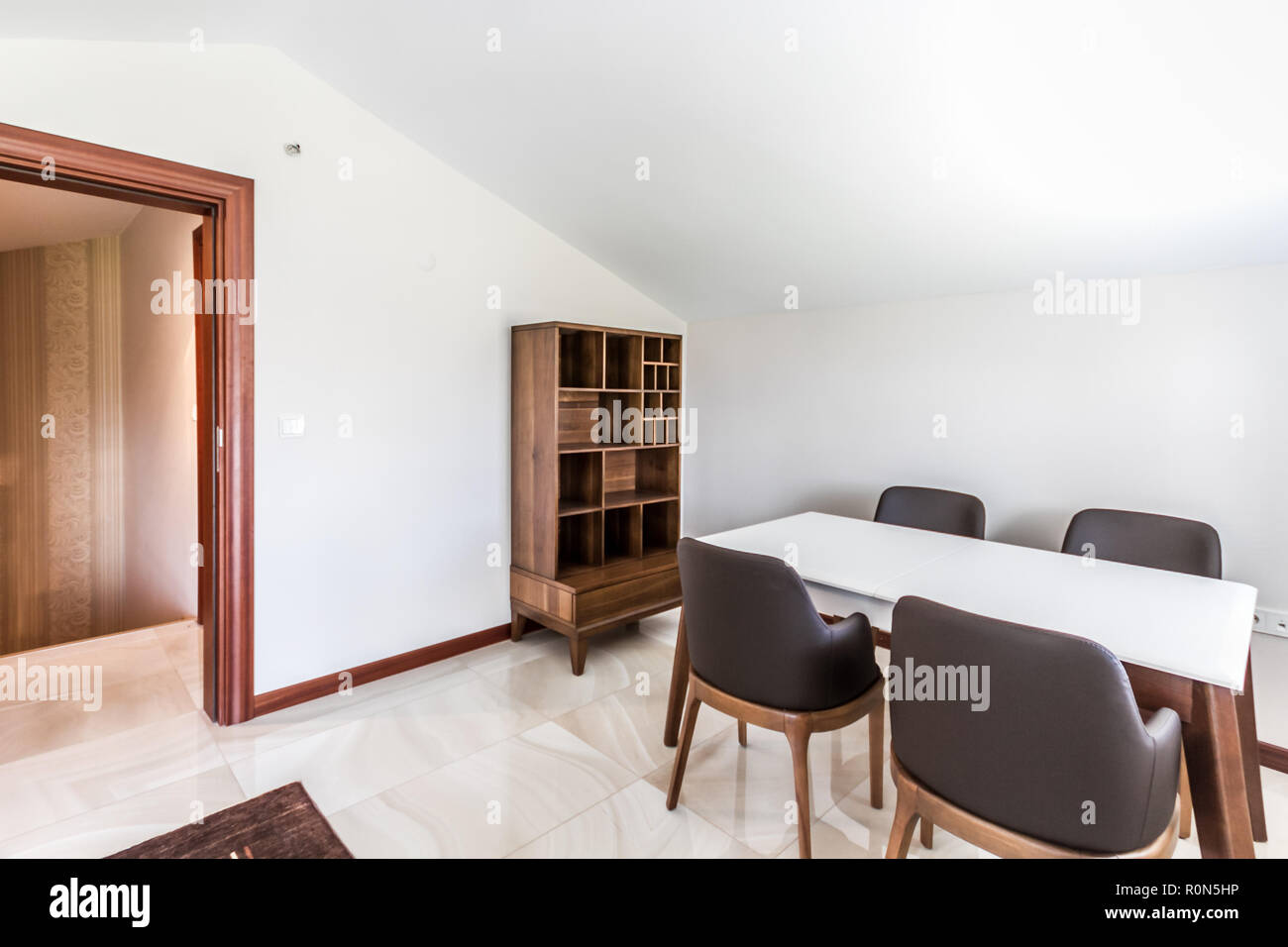 Table and chairs for multipurpose use in an attic room - Stock Image