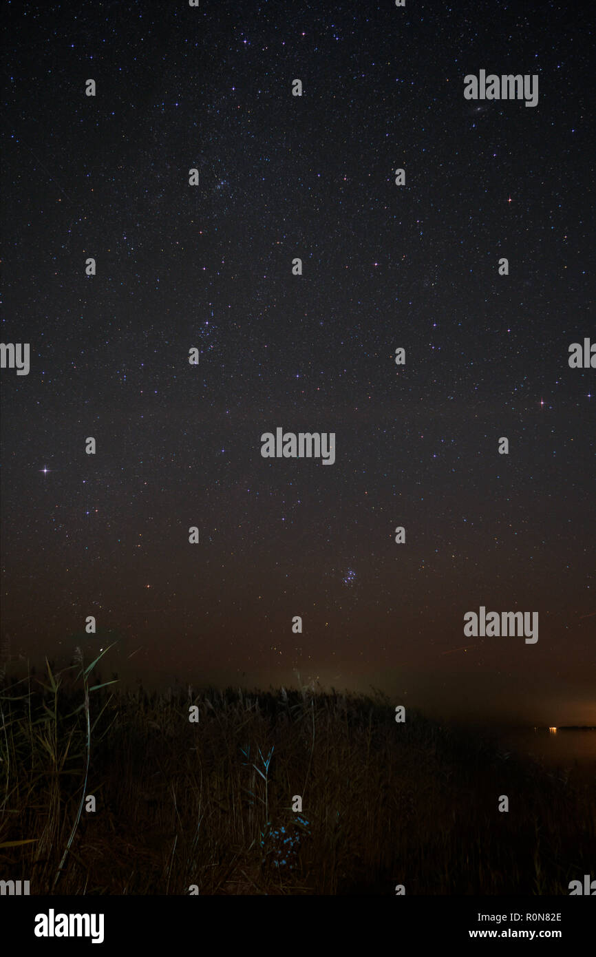 Night Sky over Fischland in Germany with Milky Way, Pleiades, Andromeda Nebula, and Perseus Constellation - Stock Image