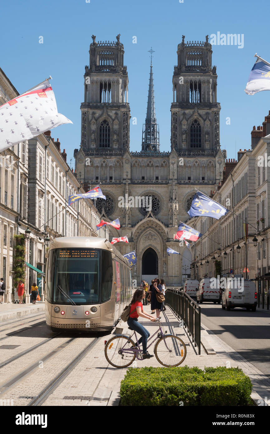 Female cyclist crossing Rue Jeanne d'Arc in front of a tram, Orléans, Centre-Val de Loire, France, Europe Stock Photo
