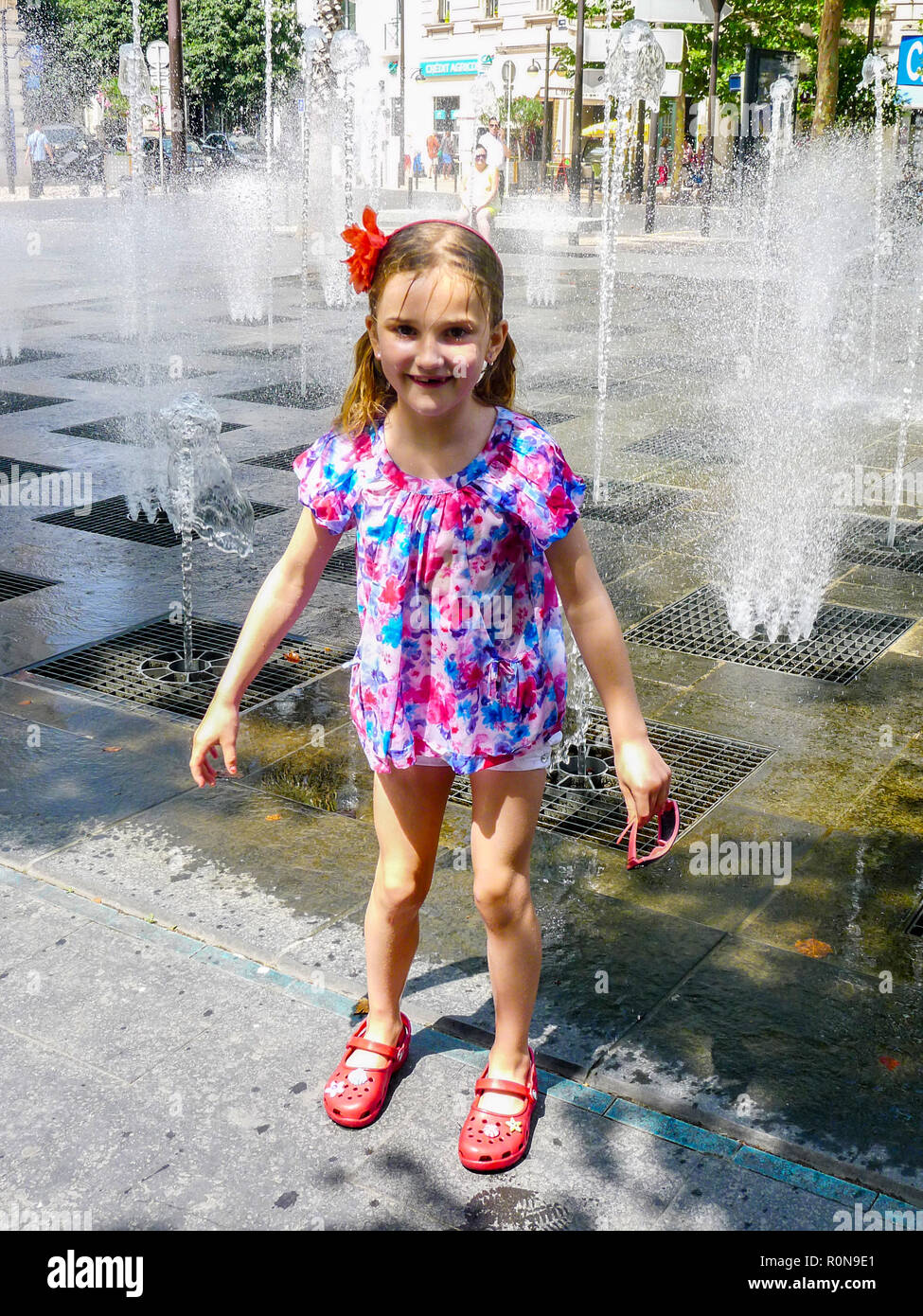 Kid Child soaked, soaking wet, playing, water fountains, water mirror Place Masséna, Nice, Cote d´Azur, France, childhood concept, time of her life - Stock Image