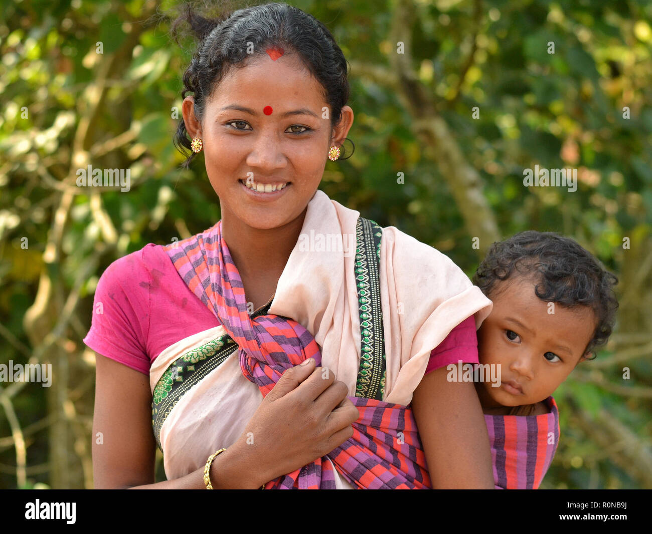 Young Northeast Indian Mishing tribal woman from Majuli Island carries her curious baby boy in a baby sling on her back. Stock Photo