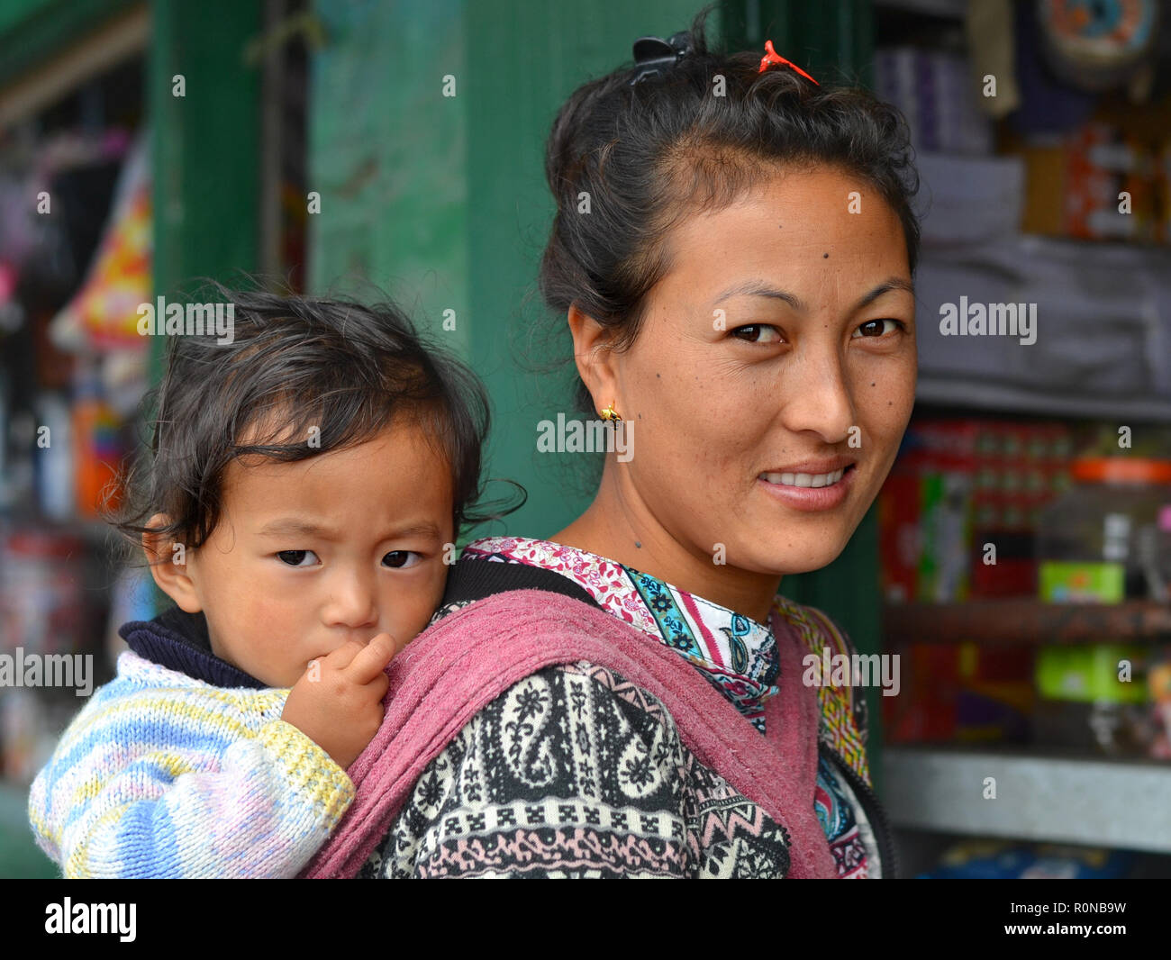 Young Northeast Indian Monpa hill-tribe woman carries her toddler boy in a traditional baby sling on her back. Stock Photo