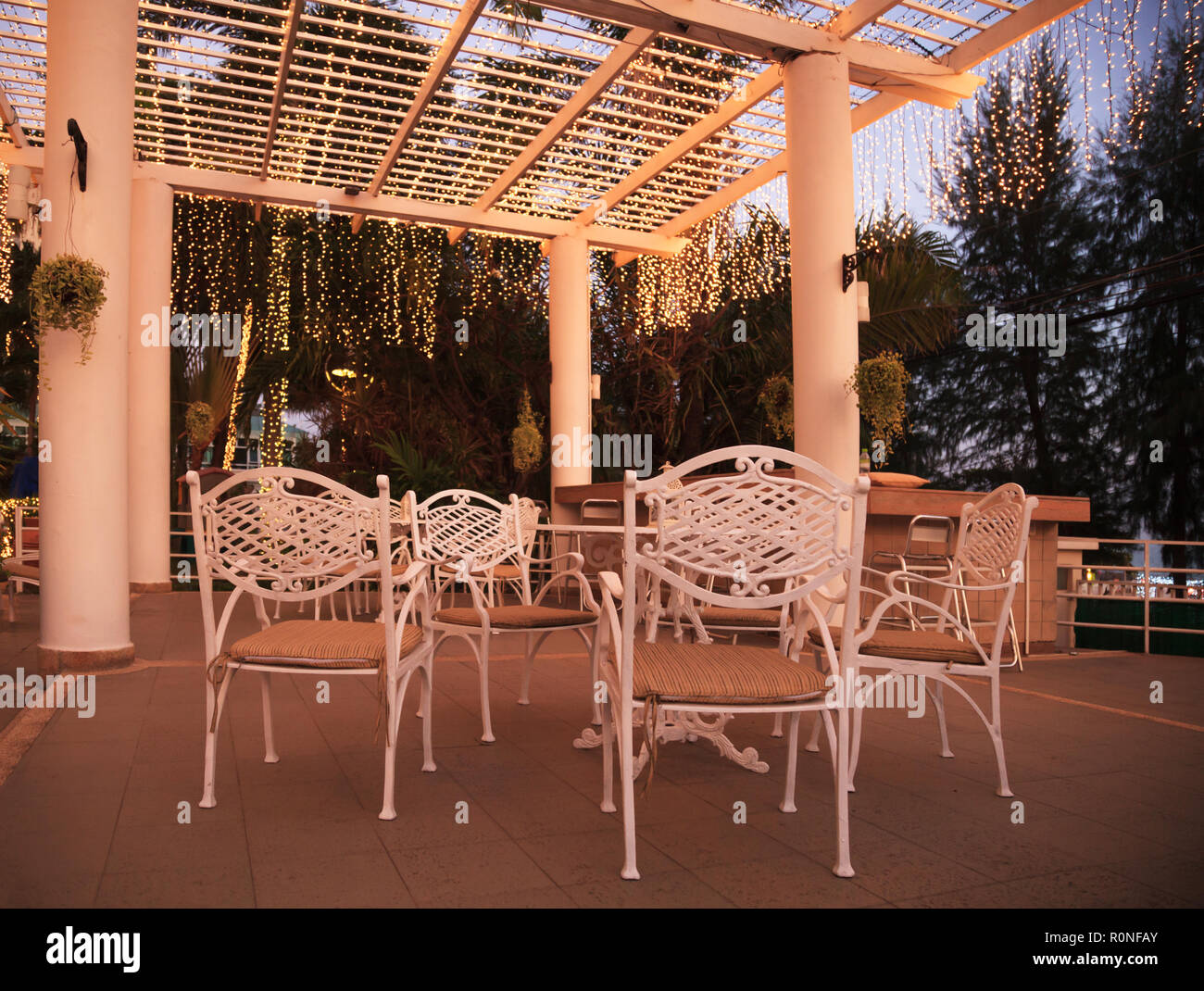 white outdoor exterior park garden party table and chairs with warm light illumination decoration ceiling, architecture house home furniture design co - Stock Image