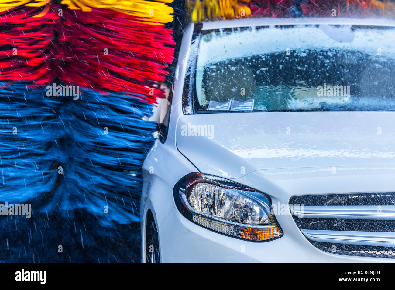 Car going through an automated car wash machine. - Stock Image
