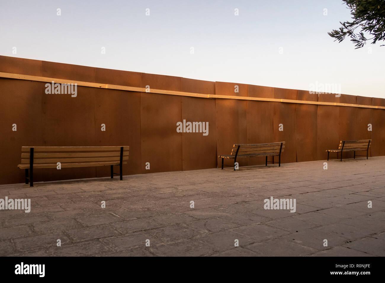 4 benches facing a fence, Malta - Stock Image