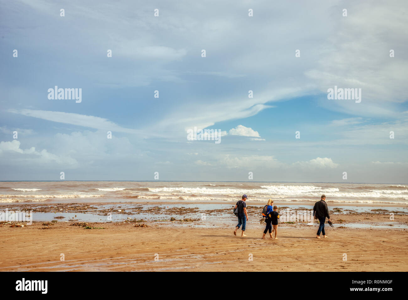 An unidentifiable family walking along a littered beach after a storm with white clouds, a blue sky, brown sand, and many waves crashing on the shore - Stock Image