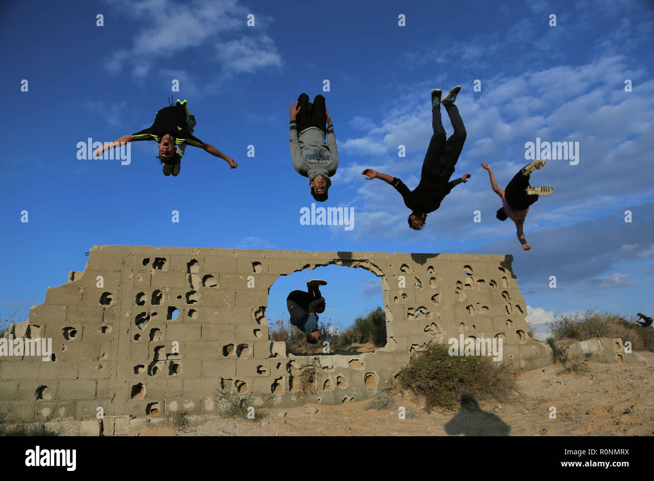 Palestinian youths are seen performing a Parkour jump together during their Parkour practice at the war-torn stones. Gaza has one of the highest youth unemployment rate in the world with over 80% of young people under the age of 30 being unemployed, Parkour is one of the ways for the youth to spend their long afternoons and keep themselves fit. - Stock Image