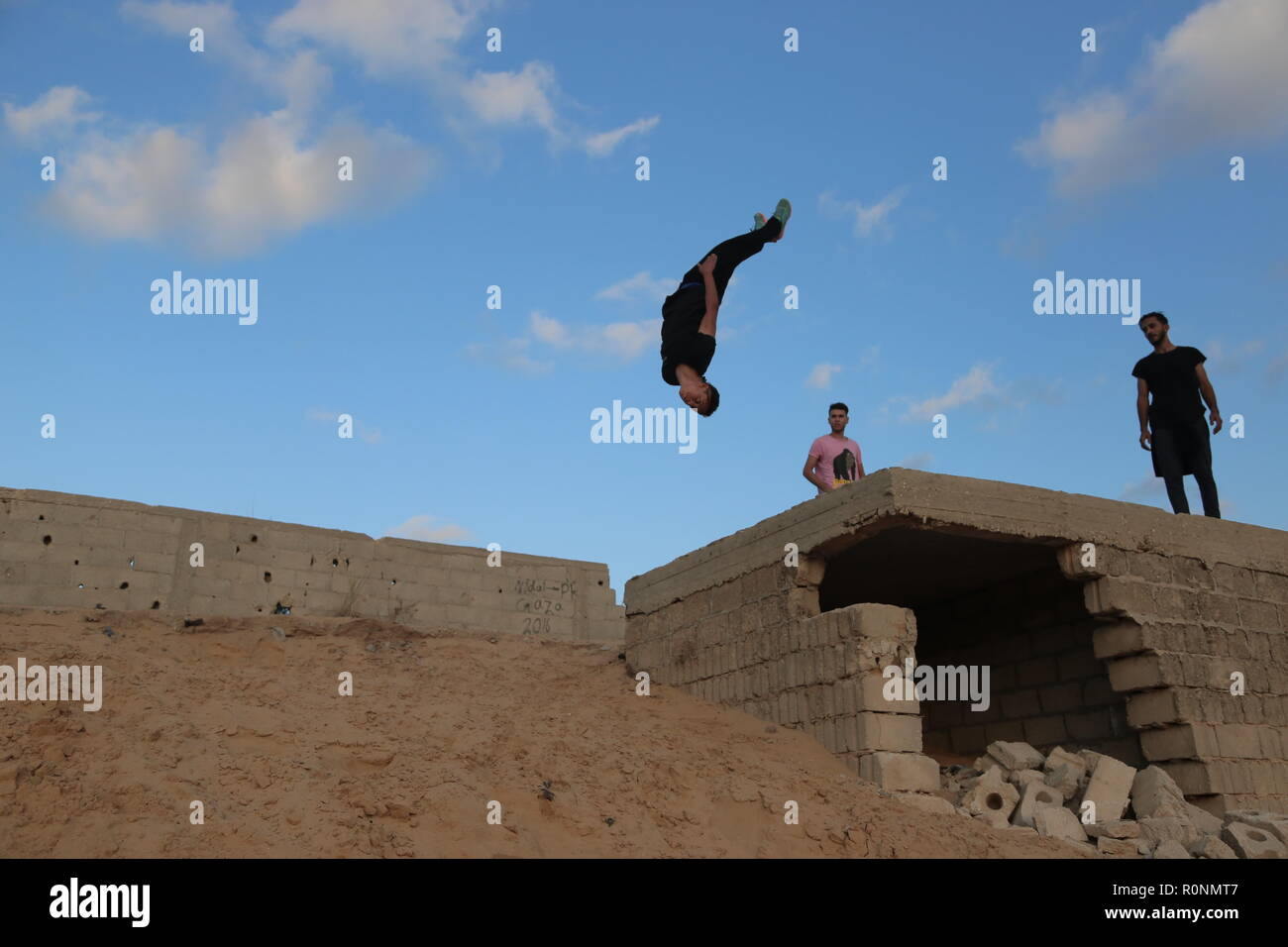 A young Palestinian man seen doing a backflip jump onto the sand hill  during their Parkour practice at the war-torn building in Gaza. Gaza has one of the highest youth unemployment rate in the world with over 80% of young people under the age of 30 being unemployed, Parkour is one of the ways for the youth to spend their long afternoons and keep themselves fit. - Stock Image