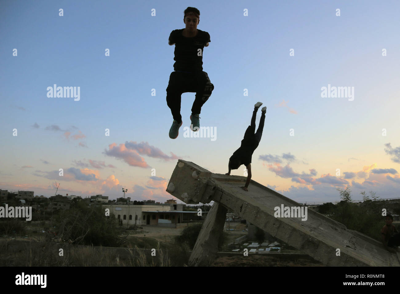 Two Palestinian youths are seen jumping high during their Parkour practice at the war-torn building in Gaza. Gaza has one of the highest youth unemployment rate in the world with over 80% of young people under the age of 30 being unemployed, Parkour is one of the ways for the youth to spend their long afternoons and keep themselves fit. - Stock Image