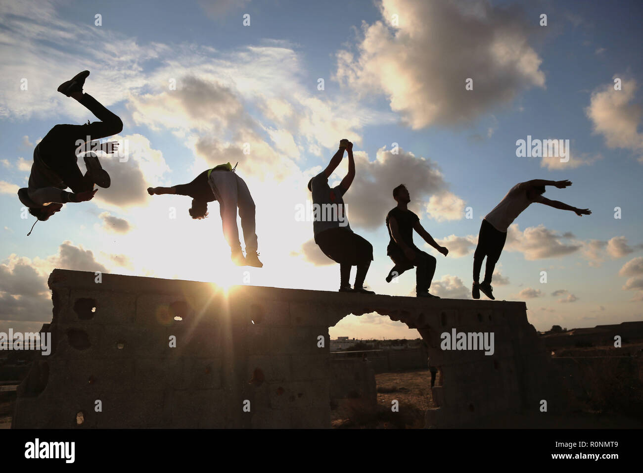 Palestinian youths are seen performing a Parkour jump together at sunset during their Parkour practice at the war-torn building in Gaza. Gaza has one of the highest youth unemployment rate in the world with over 80% of young people under the age of 30 being unemployed, Parkour is one of the ways for the youth to spend their long afternoons and keep themselves fit. - Stock Image