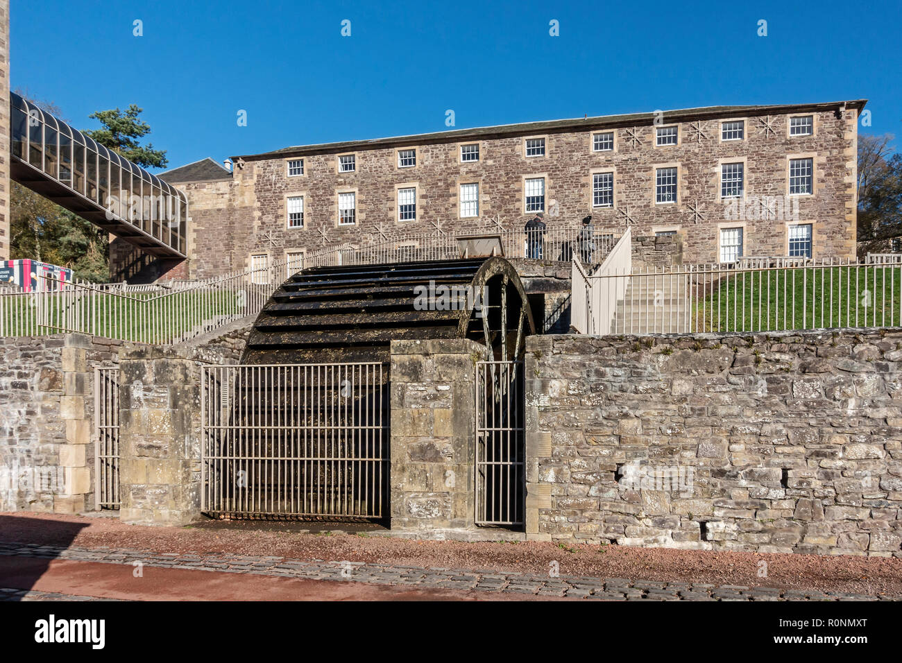 Water wheel beside Mill 3 with Institute behind at New Lanark Mills World Heritage Site by the River Clyde in Lanark Lanarkshire Scotland UK - Stock Image