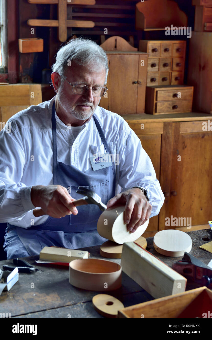 Inside Hancock Shaker Village woodworking workshop with man making a traditional oval Shaker wooden box Pittsfield MA, USA - Stock Image