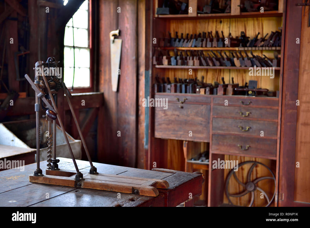 Inside Hancock Shaker Village woodworking workshop with barn beam drill press and molding planes Pittsfield MA, USA - Stock Image