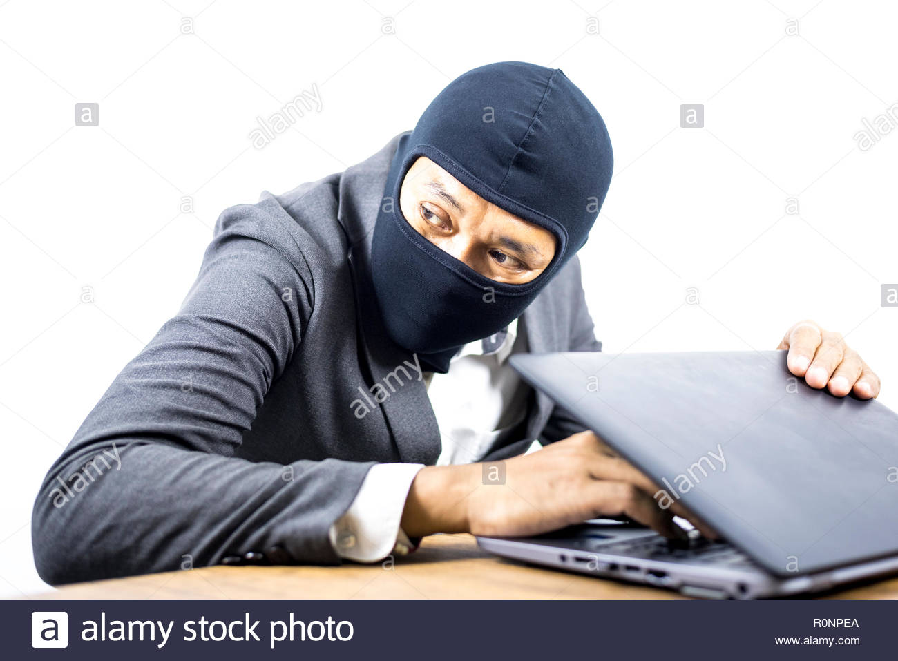 Data theft, Computer hacker stealing data and personal identity information off a laptop computer, Data center security policy - Stock Image