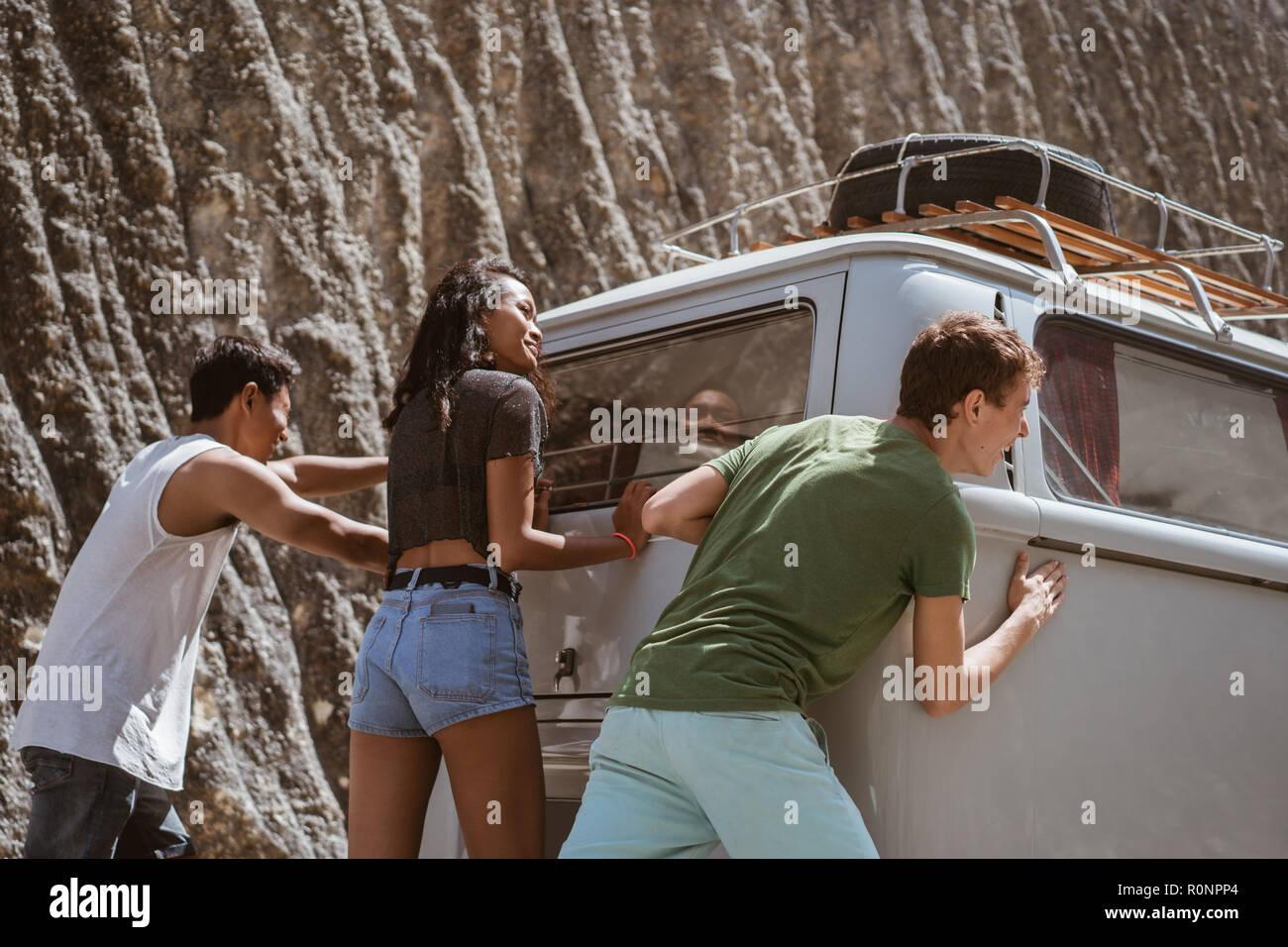 young people push broke down retro van - Stock Image