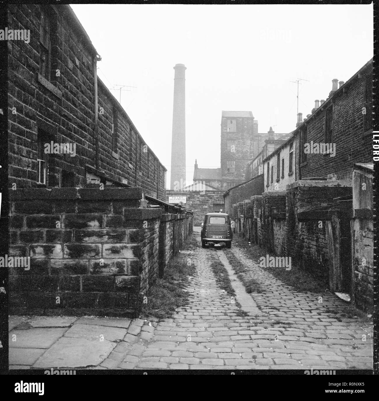 Richard Street, Burnley, Lancashire, c1966-c1974. A car parked in the cobbled ginnel (alley) running between Milton Street and Tentre Street viewed from Richard Street with Pentridge Mill and mill chimney partially visible in the background. The terraces shown here were demolished in the late 1960s. Holly House flats now occupies the site. - Stock Image