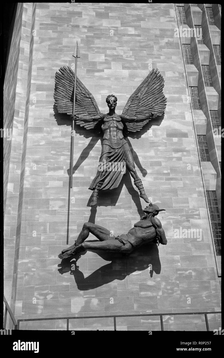 'St Michael's Victory over the Devil', sculpture at Coventry Cathedral, West Midlands, c1958-c1980. Detail of the sculpture depicting St Michael over Lucifer holding a long spear in his right hand, arms and wings outstretched, with Lucifer's feet bound by chains and his arms bound behind his back, attached on the exterior of the baptistery wall of the new Coventry Cathderal.The sculpture is by Jacob Epstein and is attached to the baptistery wall near the porch. It is hung so that Lucifer's nearly horizontal body aligns with the top of the steps that ascend towards the porch, and the top of St  - Stock Image