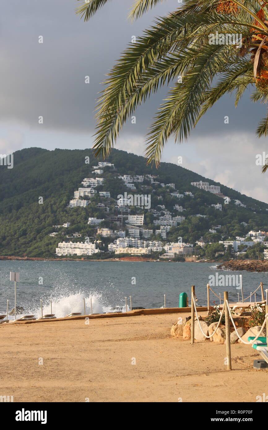 waves crashing onto the coastline and bedchairs in Santa Eulalia, Ibiza - Stock Image