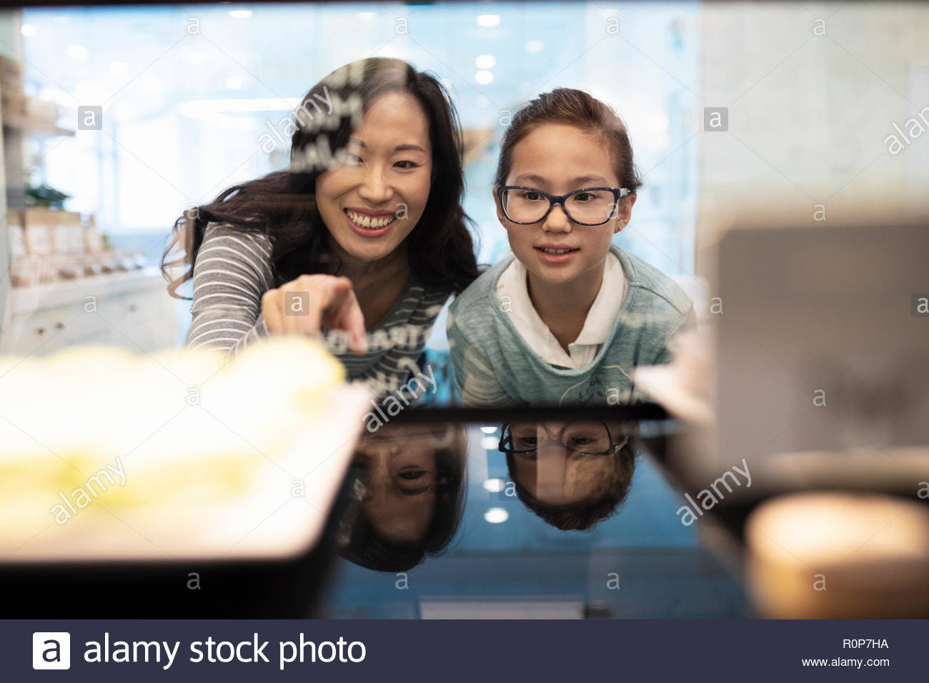 Mother and daughter eyeing cupcakes in bakery - Stock Image