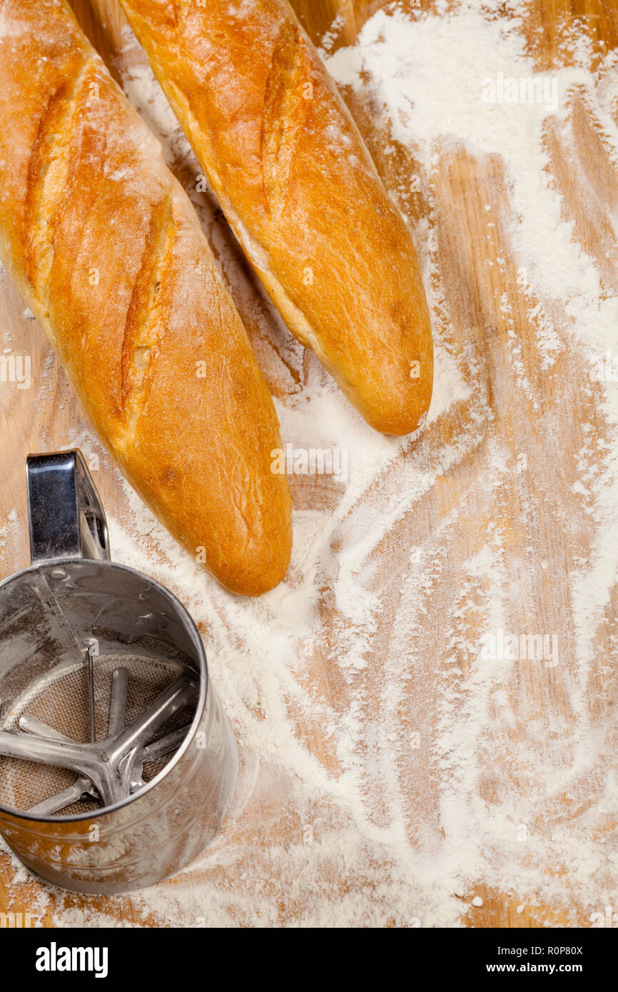 Freshly baked artisanal baguettes  (french bread) with flour sieve or sifter on wooden background covered with flour - Stock Image
