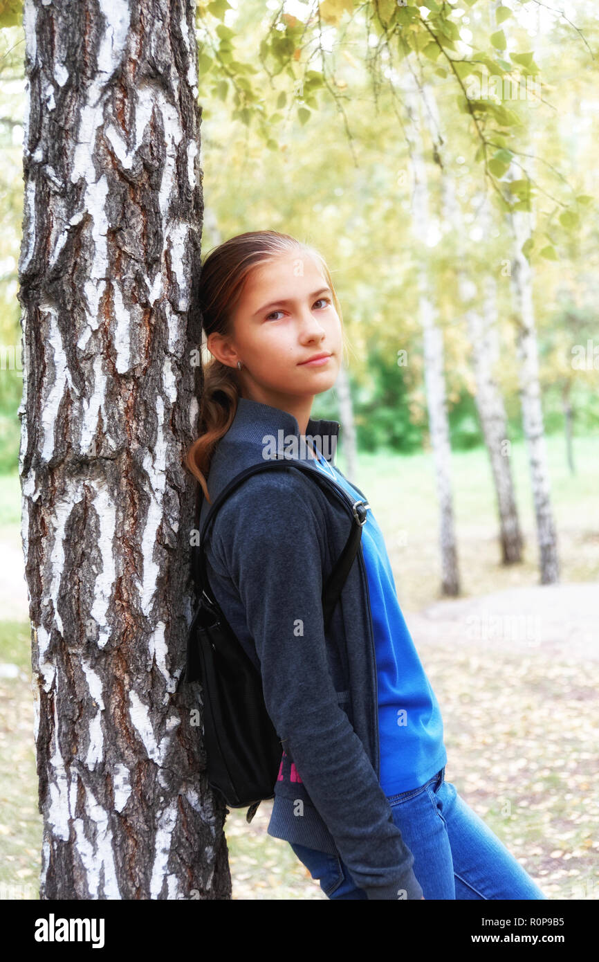 Romantic mood in a teen girl in an autumn birch grove. A kind and slightly mocking look in the camera, soft focus - Stock Image