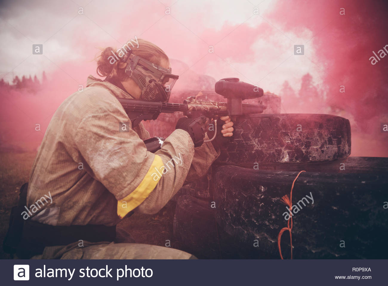 Red smoke surrounding man paintballing - Stock Image