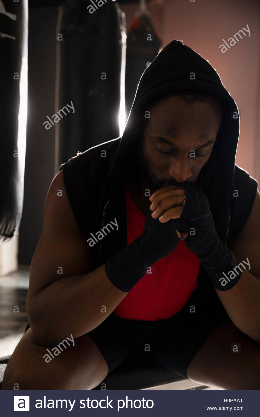 Male boxer in hoody resting in gym - Stock Image