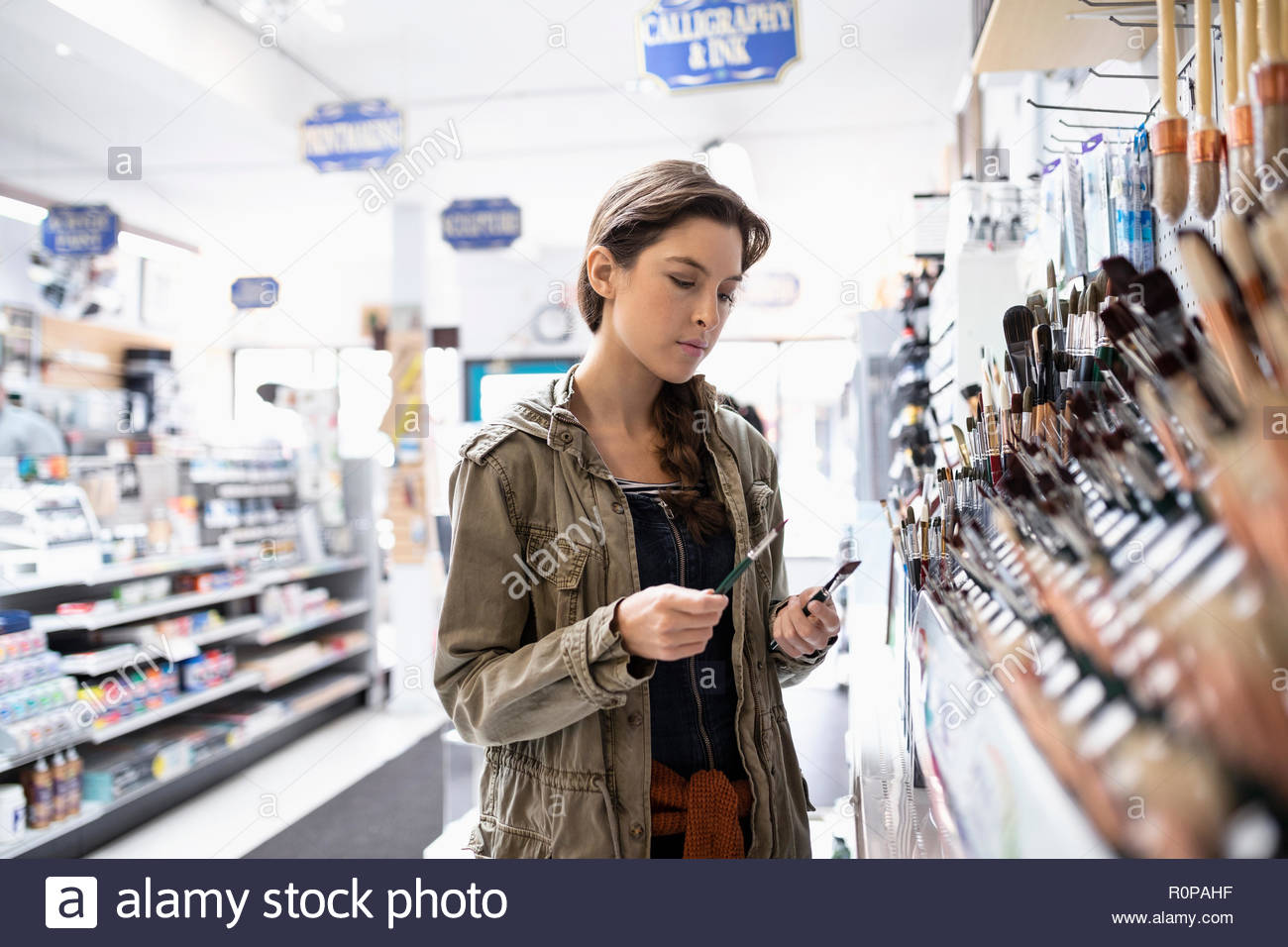 Woman shopping for paintbrushes in art supply shop - Stock Image