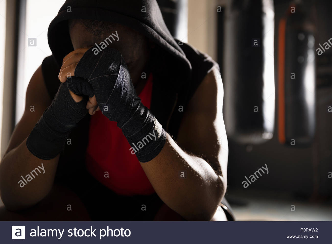 Tired male boxer with head in hands, resting in gym - Stock Image