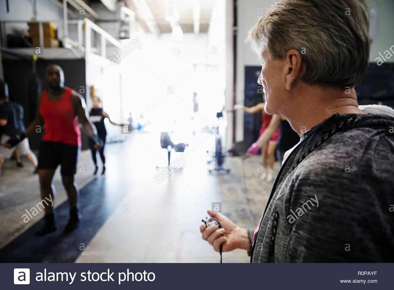 Trainer with stopwatch timing male boxer jump roping in gym - Stock Image