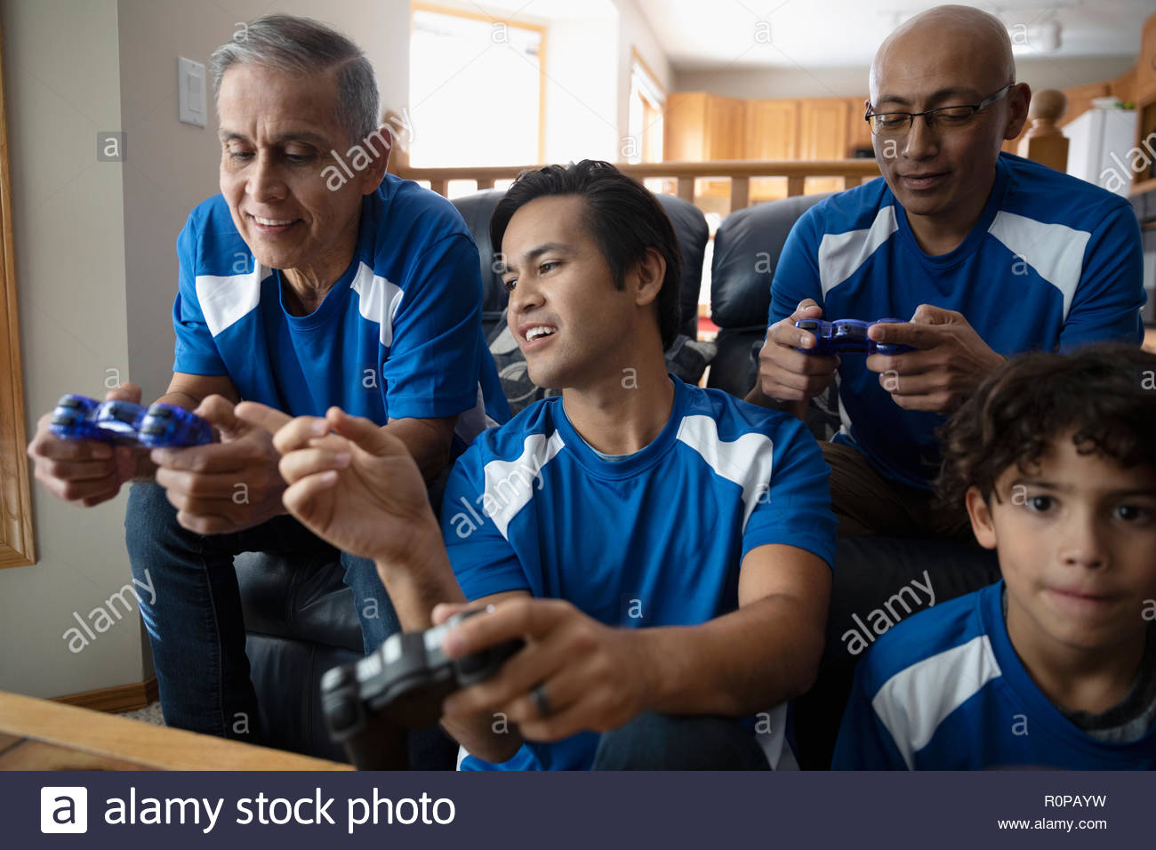 Latinx multi-generation family playing sports video game Stock Photo