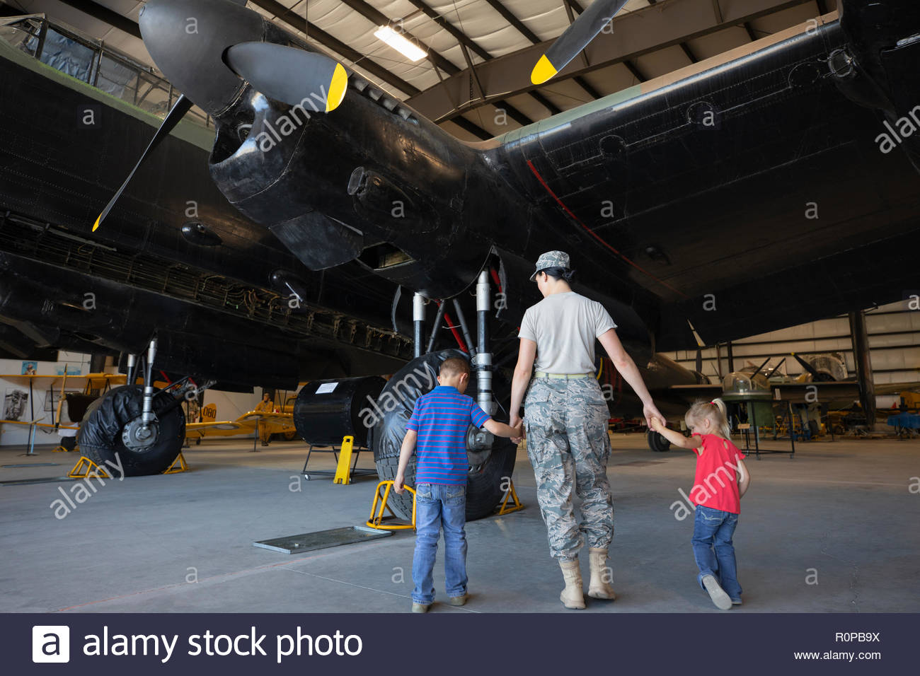Female army engineer mother walking with children in military airplane hangar - Stock Image