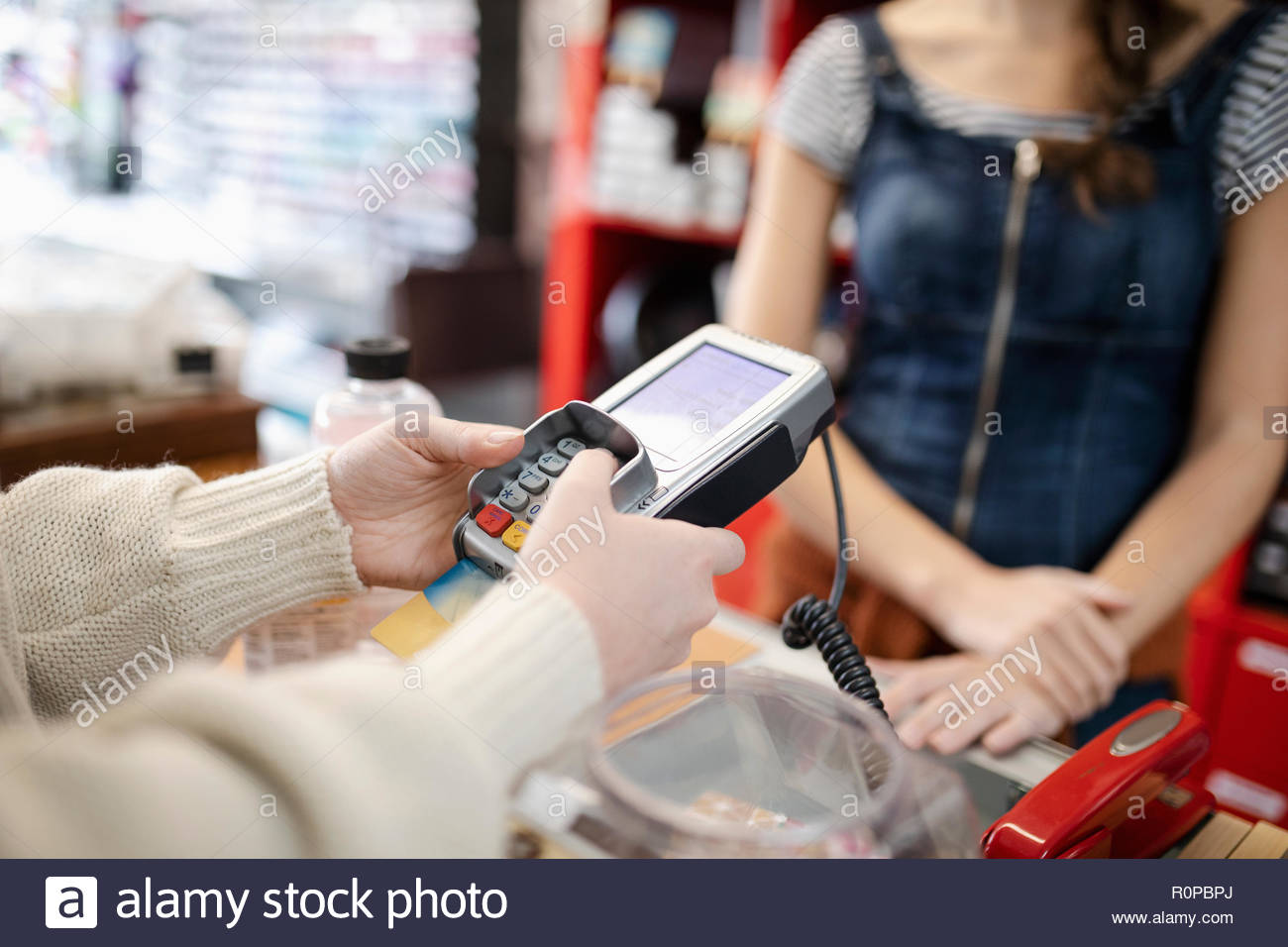 Close up female shopper paying, using credit card reader pin entry - Stock Image