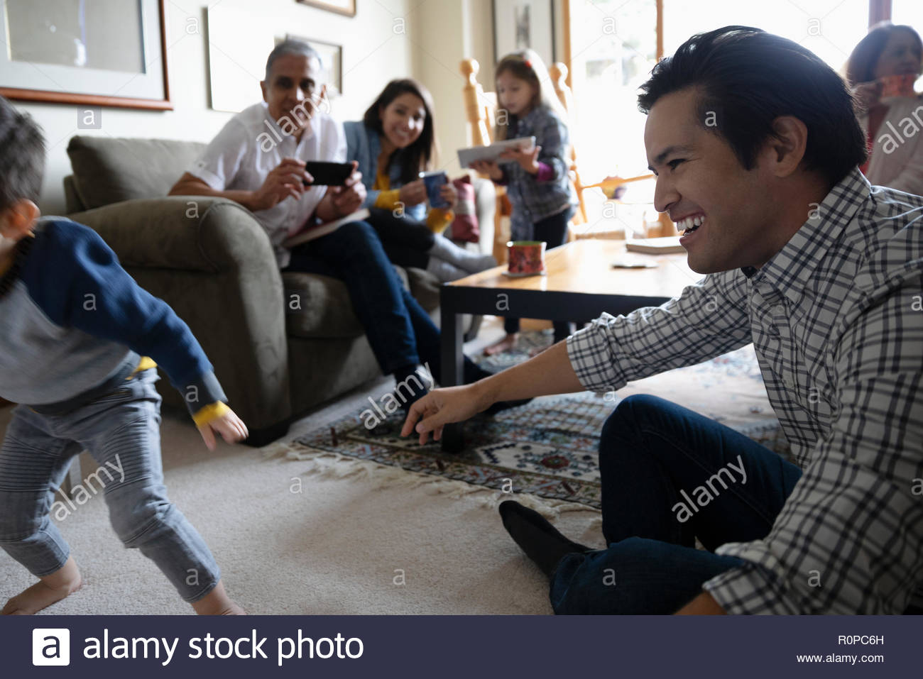 Latinx multi-generation family playing in living room - Stock Image