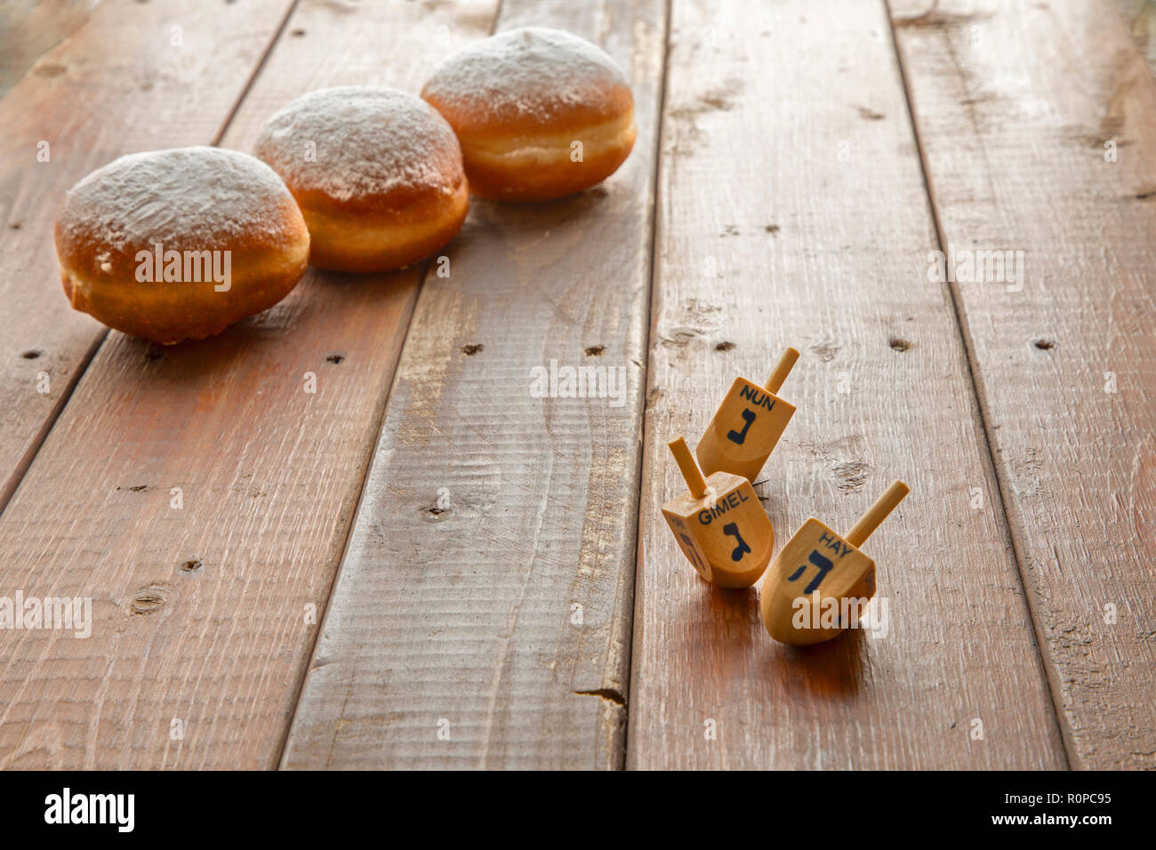 Still life for jewish holiday Hanukkah with 3 donuts and 3 dreidels on wooden rustic table.Hanukkah celebration concept.Shallow DOF Focus on the Deidl - Stock Image