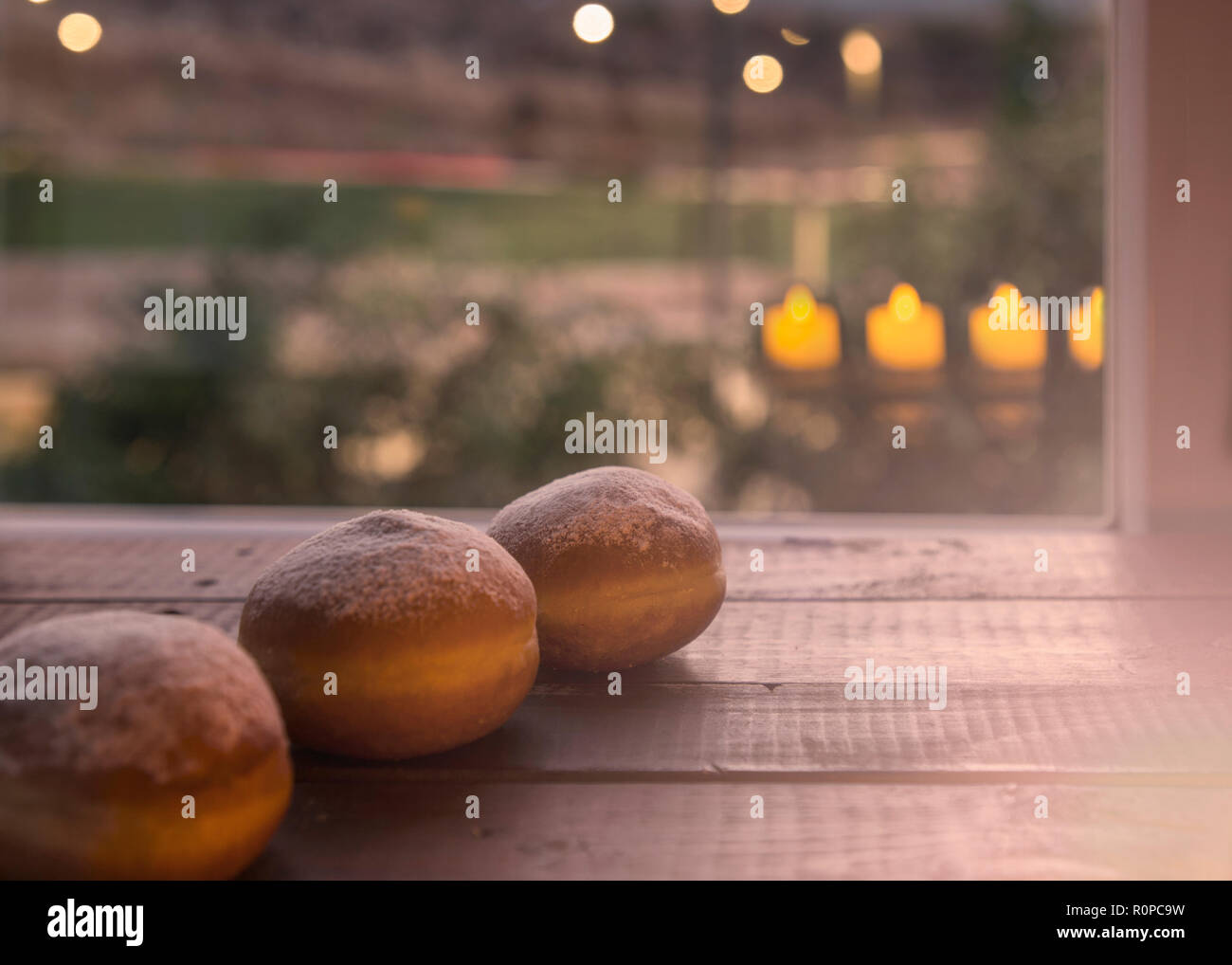 Still life for jewish holiday Hanukkah with 3 Donuts and Candlelights Reflection on the Window.Shallow DOF.Hanukkah celebration concept. - Stock Image