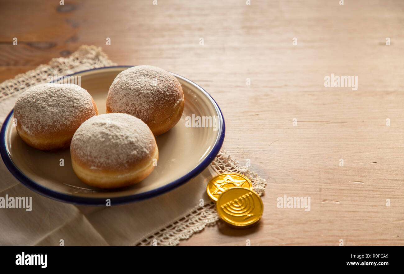 Still life for jewish holiday Hanukkah with donuts and chocolate coins on White vintage Serviette on wooden table.Hanukkah celebration concept - Stock Image